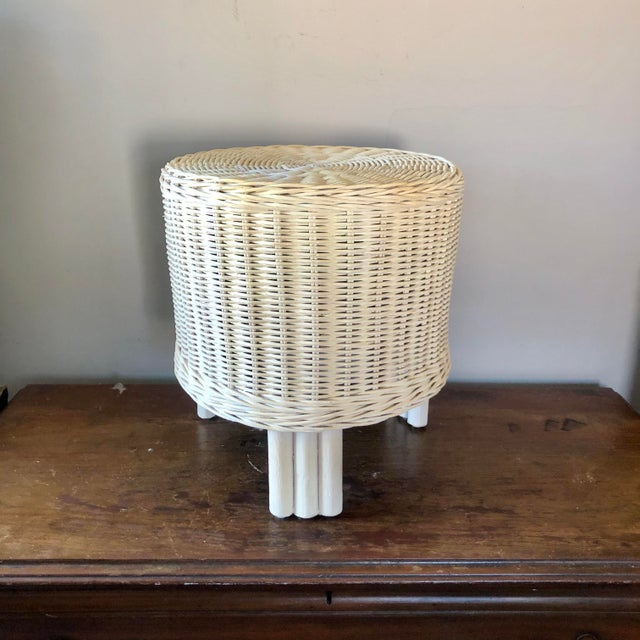 A pair of white wicker pouf stools.