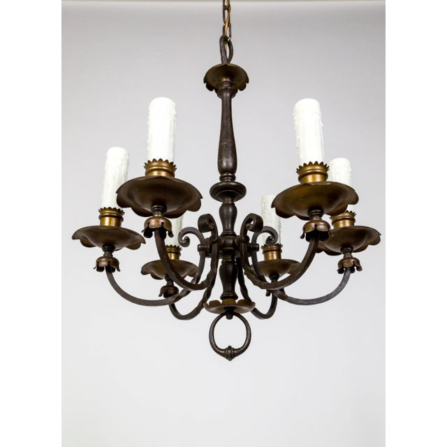 A brass and painted bronze Renaissance Revival chandelier with six scroll arms, with scalloped bobeches; in rich shades of...