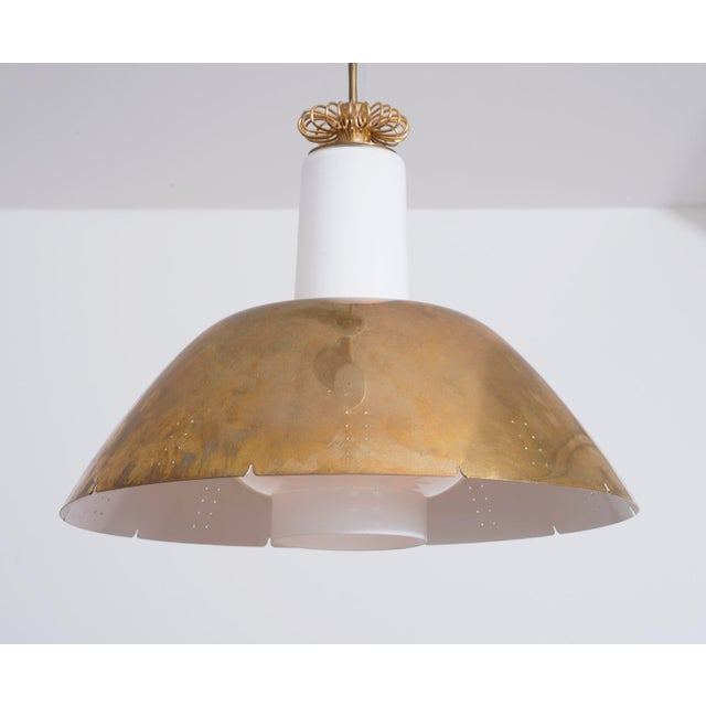 Paavo Tynell pendant for Idman Oy in nicely patinated brass with white glass diffuser. Classic Tynell perforations in...