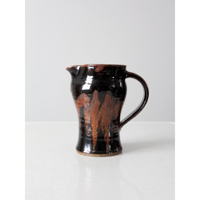 This is a vintage studio pottery pitcher. Artist signed, the ceramic pitcher has an elegant shape with dark brown near...