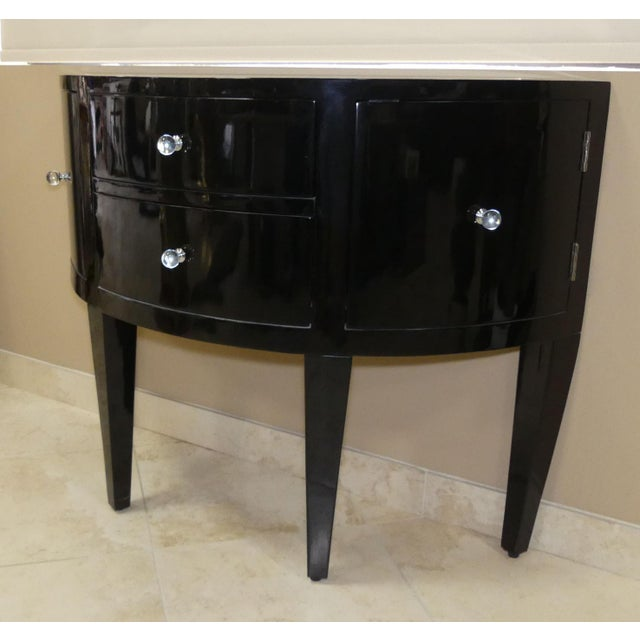 Stylish and modern black lacquered demilune console. Features a sleek shape on tapered legs. 2 drawers and 2 doors with...