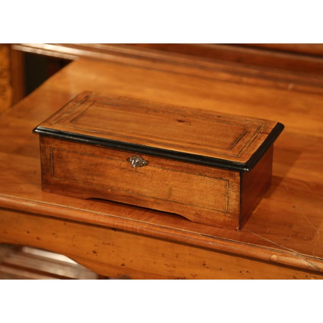 This beautiful, antique music box was crafted in France, circa 1860. The walnut music box has an inlay band and black...