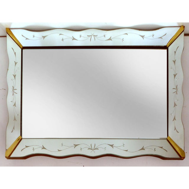 A rectangular 1940's wall mirror with a scalloped mirror frame decorated in elegant wheel-cut floral motifs. The corners...