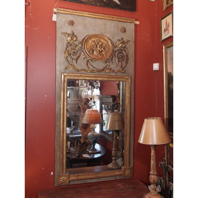 French 19th century trumeau mirror. Louis XVI Style. Circa 1850. Painted in a pale green with carved gilt wood floral...