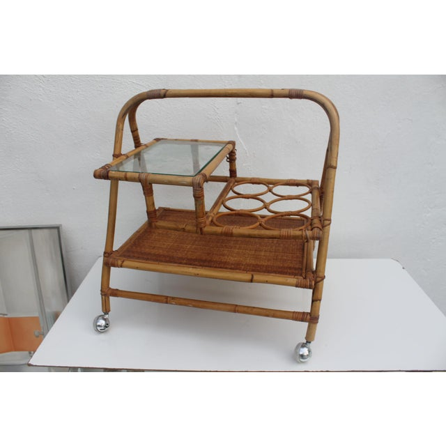 Vintage mid-century modern wicker and rattan small rolling tea cart. Circa of 1970's . In excellent vintage condition with...