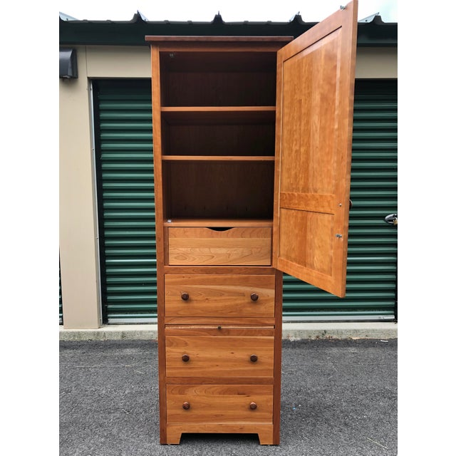 A solid cherry shaker style armoire dresser with ample drawer space as well has adjustable shelving.