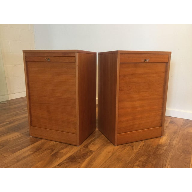 Two similar Danish Modern teak file cabinets with roll down tambour doors. One has two pull out spaces for hanging files...