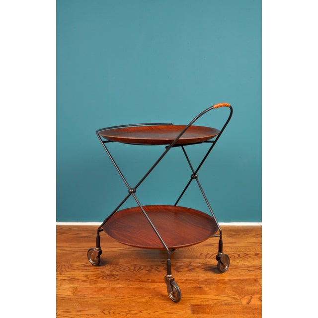 A tidy collapsible wheeled cart with two teak platters. Remove the platters to collapse and store away. May also be used...
