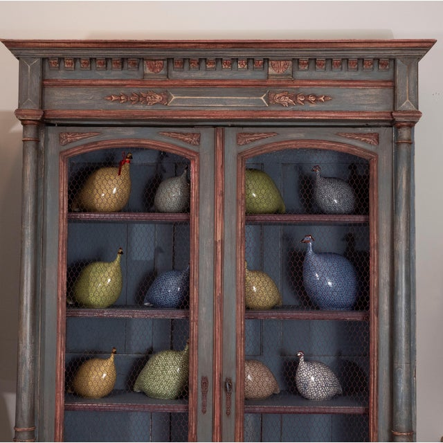 An early 20th century French painted bibliotheque with intricate carving and chicken wire doors. It has many architectural...