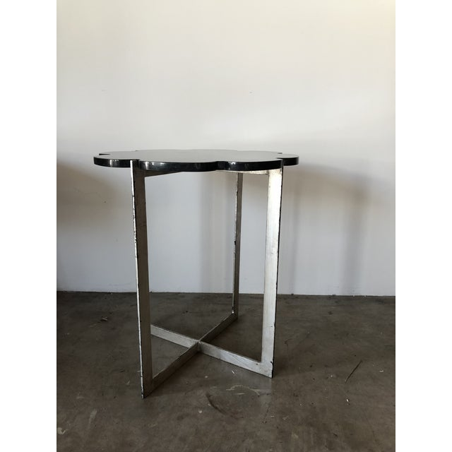 Scalloped edge, polished stone topped table with striking silver leaf base.