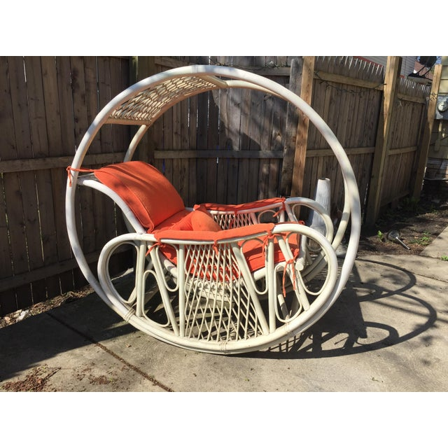 Vintage rattan rocking chair, white with an orange/coral cushion and accent pillows circa 1960's. Made in the style of...