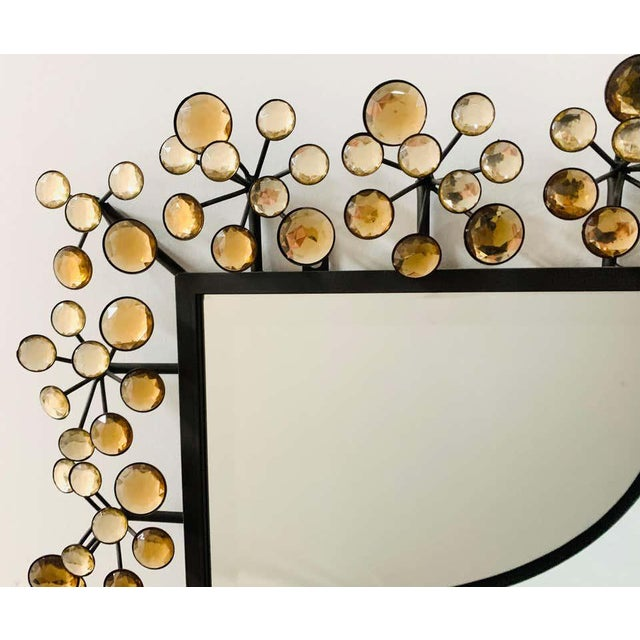 A Mid-Century Modern accent beveled wall mirror with faux yellow crystal design. The metal frame is painted in black and...