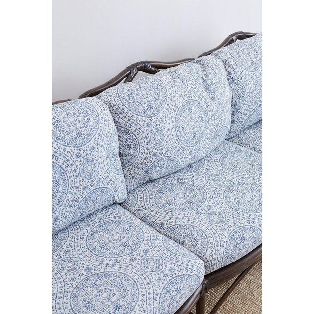 Stunning McGuire organic modern bamboo rattan sofa featuring blue and white organic upholstery with an Indian inspired...