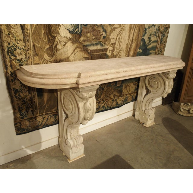 This elegant French honed marble topped console has stunning, exaggerated, volute shaped legs made of reconstituted stone....