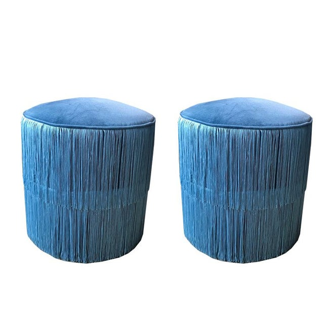 Beautiful soft round ottoman covered in luxurious blue velvet. Features two layers of fringe that wrap around the top and...