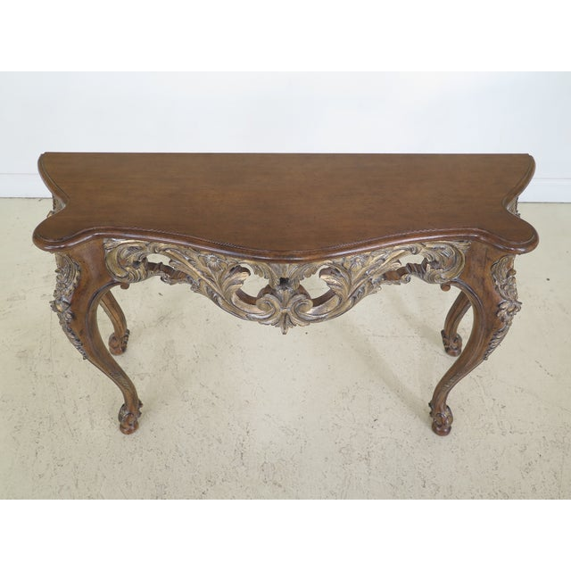 Italian carved console table w. gold highlights, about 15 years old. Nice pierced carved skirt. Walnut finish. Un-Marked...