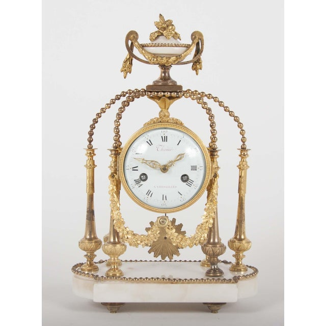An 18th Century French gilt bronze Portico clock with six columns culminating in floral urn with white enamel face; all on...