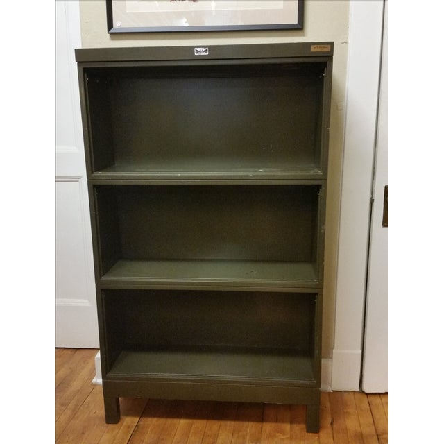 This listing is for an army green metal industrial stacking bookcase. The original pull down doors are no longer present....