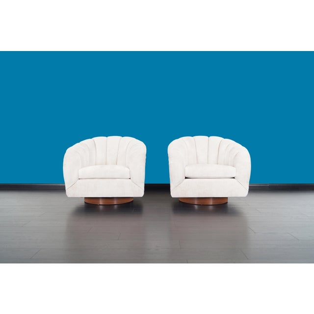 Fabulous pair of vintage swivel lounge chairs designed by Milo Baughman for Directional. Each chair has a circular walnut...