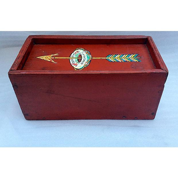Antique wood money box with sliding lid which features a hand painted arrow which points through a ship's life preserver...