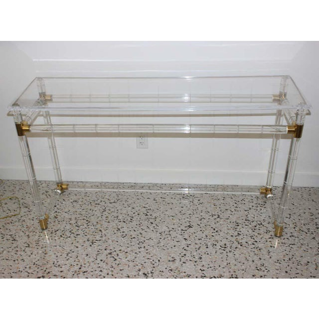 This stylish lucite and brass console table was designed by Charles Hollis Jones and it dates to the late 1970s-1980s.