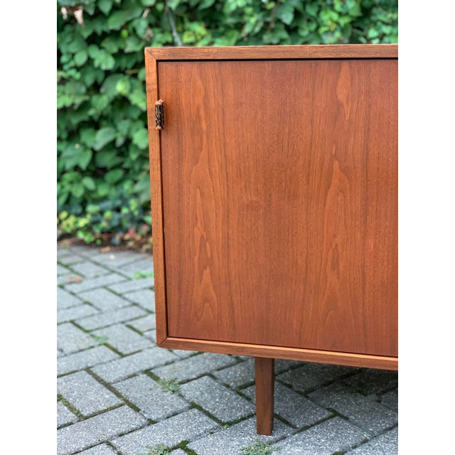 Rare midcentury classic sideboard cabinet designed by Florence Knoll for Knoll Associates. Knoll label marking. Walnut...