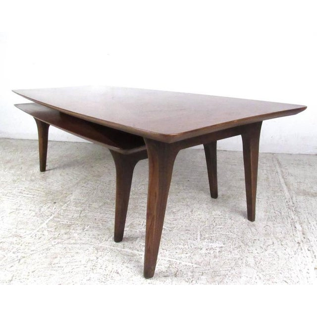 This beautiful American walnut coffee table features unique tapered legs, sculpted top, and swivel out second tier....