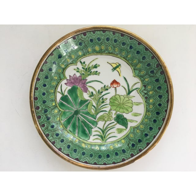 Offering a Japanese, vibrant colored, hand painted, floral Lotus design on a white porcelain bowl/catchall, encased in...