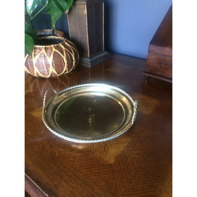 Vintage brass round tray with stylized rope detail on the edge and handles. A terrific piece to use for serving! Please...
