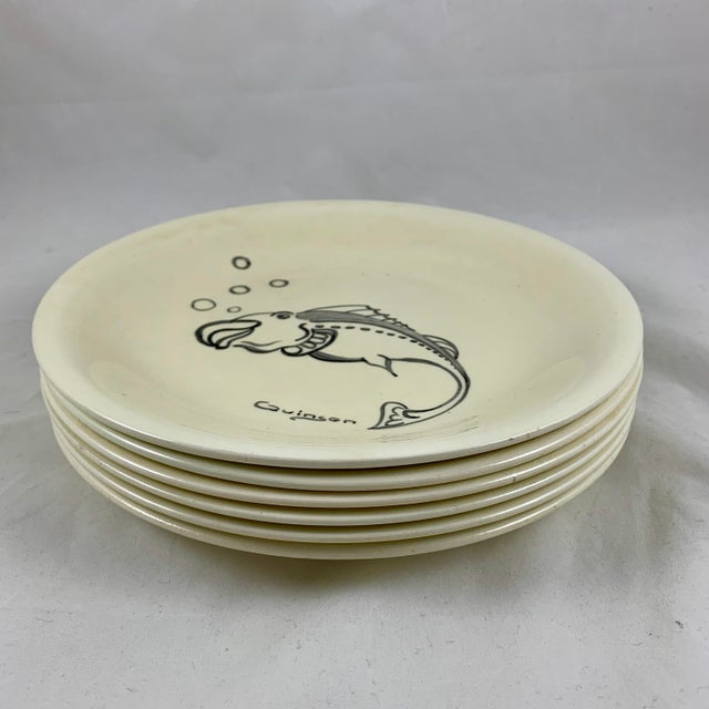A set of six Mid-Century French pottery fish plates, hand-painted by the ceramist Paulette Quinson, (1899-1984) Beginning...