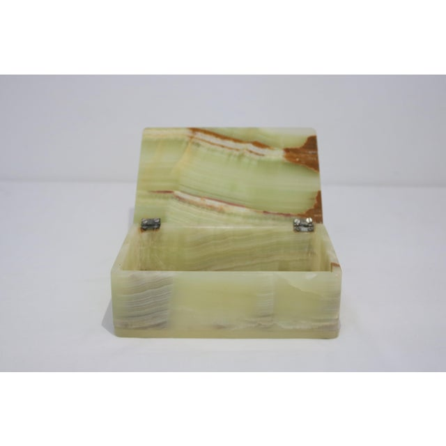 This is a Mid-Century onyx box in hues of green and terracotta.