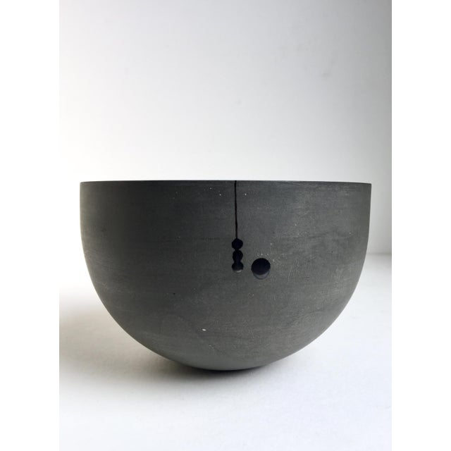 Unique charcoal gray matte finish porcelain circular vessel with graphic design of a line and dots in black glaze on front...
