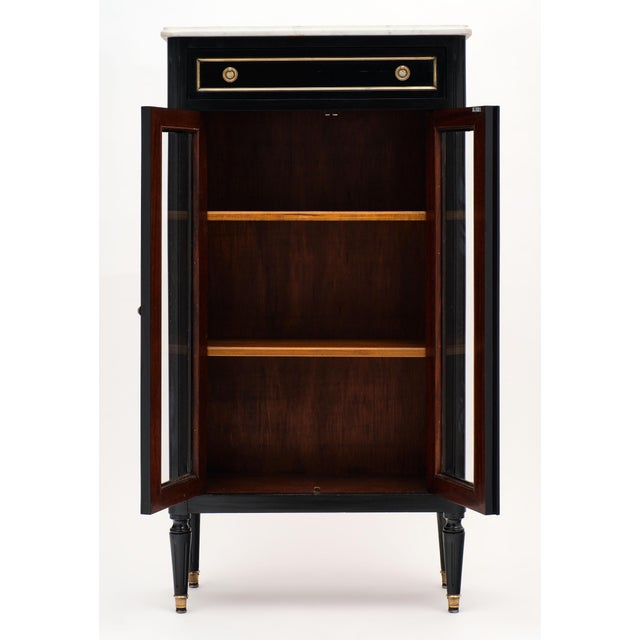 Petite ebonized Louis XVI style bookcase with classic French elegance and two glass doors trimmed in brass. There is also...
