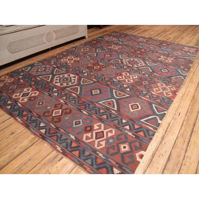 A classical Caucasian kilim, not old enough to be antique but almost there. A softer and cooler color palette.