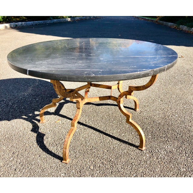 Sophisticated gilt and red wrought iron coffee table with black marble top. The marble has white lines and is very...