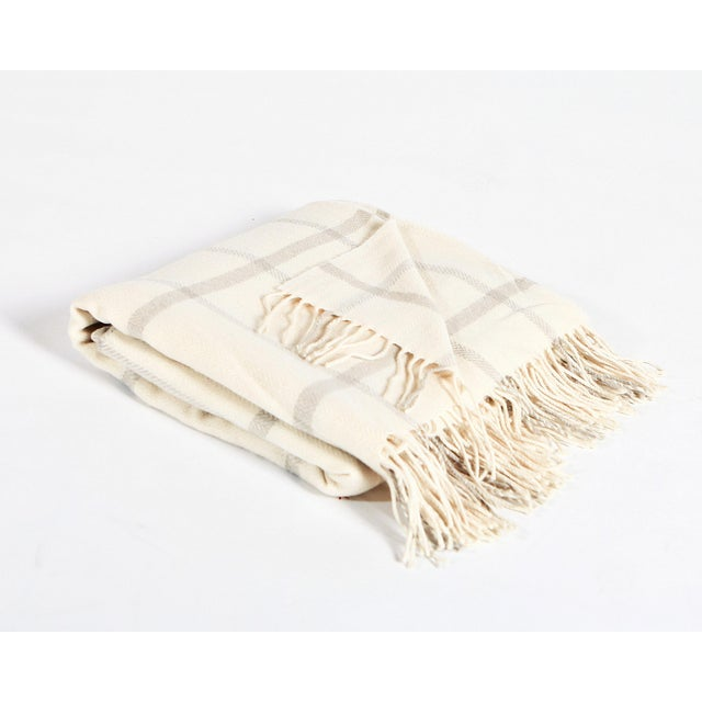 This Cream & Beige Windowpane Simply Birch Throw is made of 100% lambswool, is 78″L x 57″W and is composed of a cream...