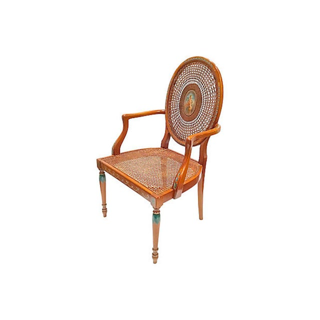 Vintage wood and cane cherub hand-painted armchair. The oval back has caning radiating from a central medallion...