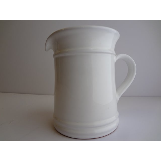 A pristine, likely vintage white glazed ceramic pitcher by Goldsmith. With the manufacturer's logo etched in the base, no...