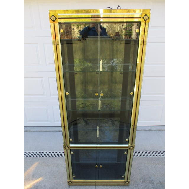 A classic brass and black lacquer lighted display case by Mastercraft. There is a set of upper and lower glass cabinet...