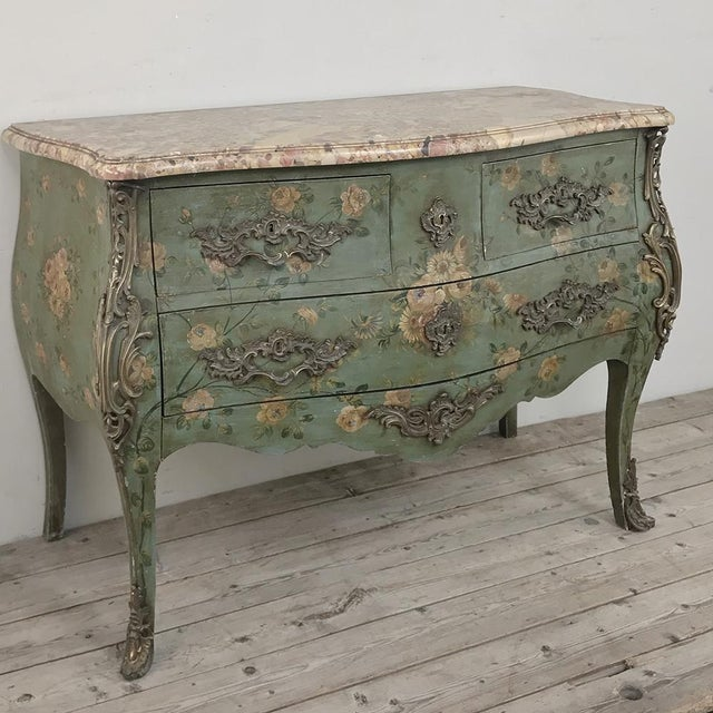 19th Century French Louis XV Painted Marble Top Commode is a study in soft pastel colors as well as the naturalistic bombe...