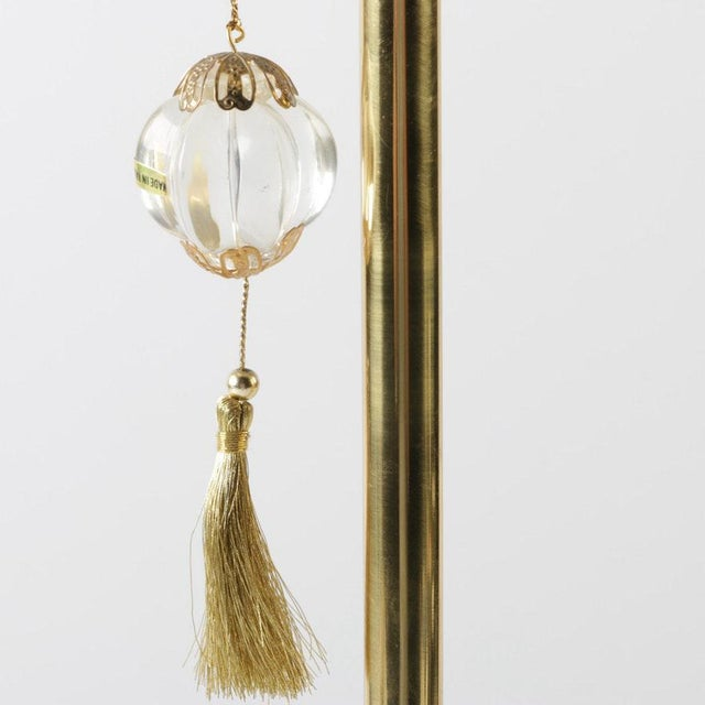 A brass accent lamp. The lamp has a brass candlestick body with a twisted sphere accent at the top. The lamp is attached...