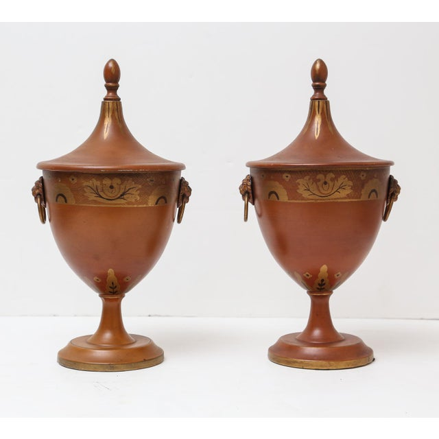 Superb pair of Continental tole ware covered chestnut urns with shaped tops, finials, and loop ring lion handles. Nice...