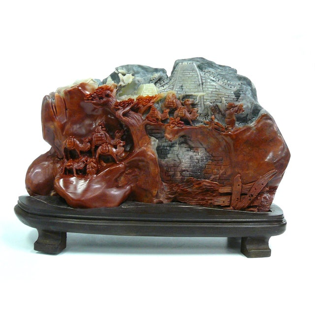 An organically-shaped sculpture featuring a Great Wall of China-themed carving. The entire piece is carved from Chinese...