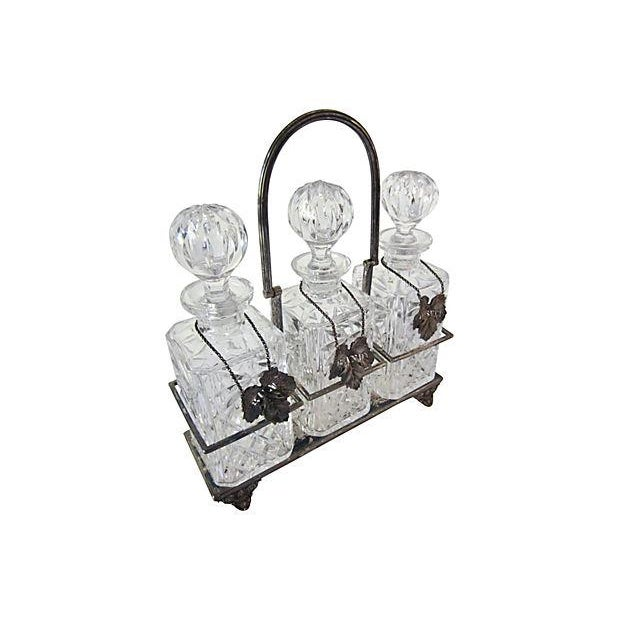 Vintage three bottle crystal decanter set with silver plate carrier container and silver plated liquor labels, one of...
