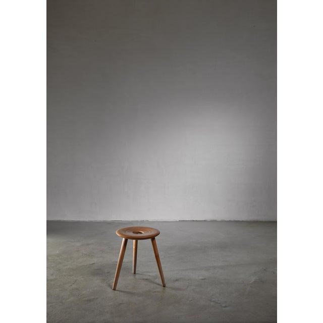 A model 'EL 121' tripod stool by Eduard Ludwig. This light laminated wood stool stands on three elegant feet. Eduard...