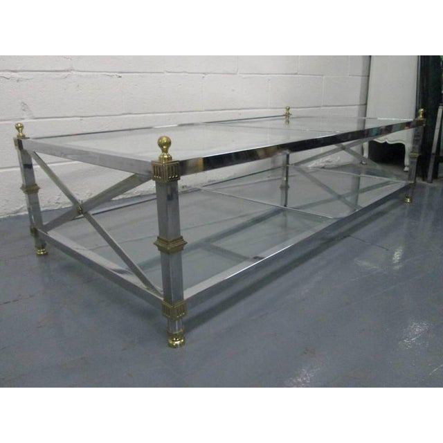 French coffee table. Table has X-stretcher to the sides, with brass and chrome frame. Top and bottom tiers have two pairs...