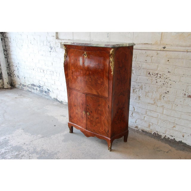 Offering a gorgeous 19th century French marble top inlaid abattant secretaire. The secretaire features a beautiful beveled...