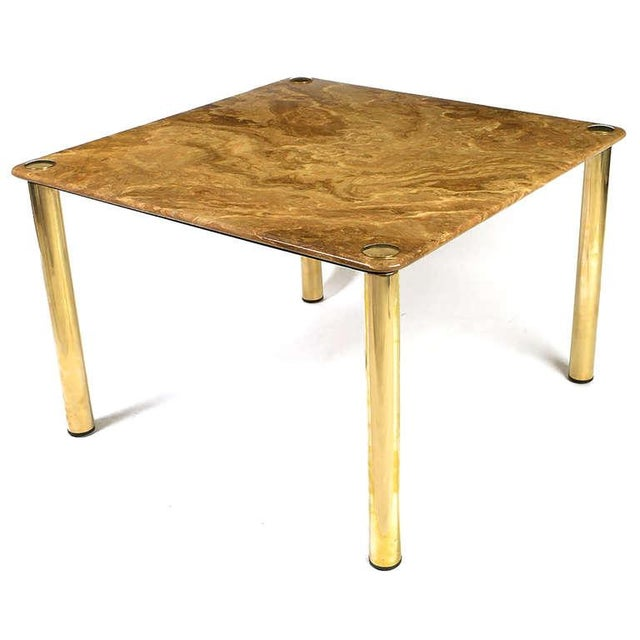Beautifully veined tawny onyx, supported by a thick steel substructure, tops this table. Four heavy brass legs provide...