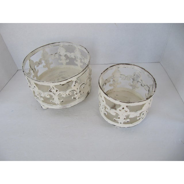 Pair of heavy metal painted, distressed fleur de lis candle holders. Great for inside or out.