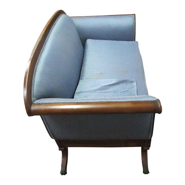 A claw foot sofa. Legs need to be reinforced. The blue upholstery is a little worn.